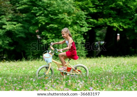 Young girl on the bicycle - stock photo