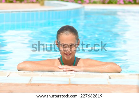 young girl on the edge of the pool - stock photo