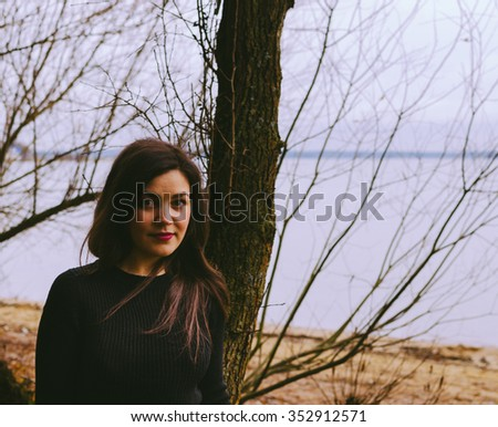 Young girl on the lake beach in autumn time