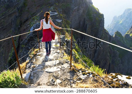 Young girl on the winding mountain trekking path at Pico do Areeiro, Madeira, Portugal - stock photo