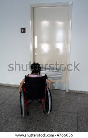 Young girl on wheelchair entering wc for disabled people