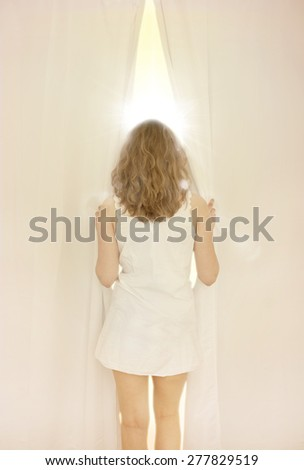 Young girl opening curtain and looking out the window on a sunny morning - stock photo