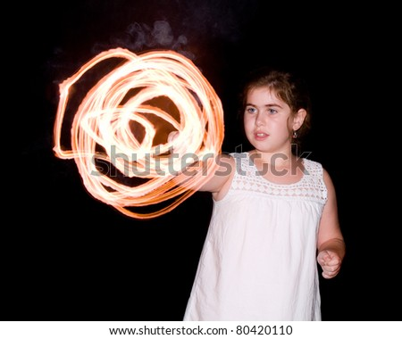Young girl or kid spinning sparker while celebrating Independence Day on July 4th.
