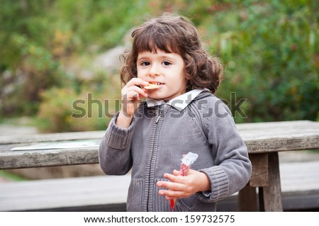 Young girl outdoor portrait in the park while eating biscuits. - stock photo