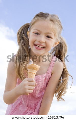 Young girl outdoors eating ice cream cone and smiling - stock photo