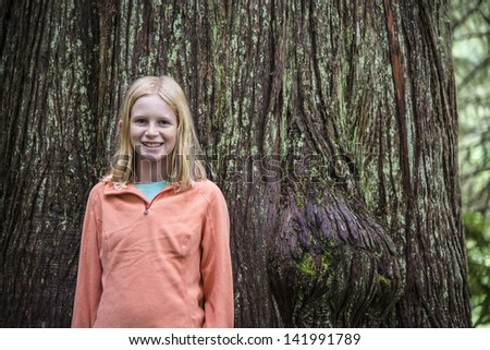 Young girl outdoors in forest, standing by a huge tree trunk