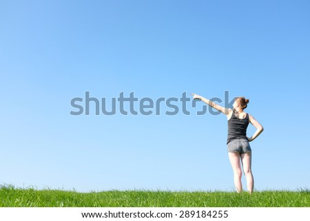 Young girl outdoors in meadow points to sky - stock photo