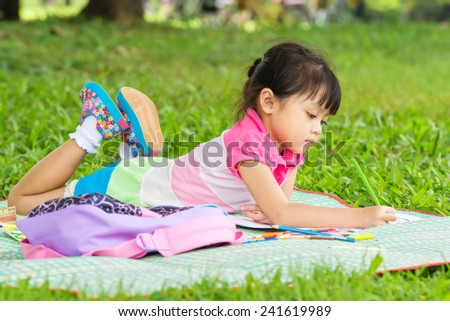 Young girl outdoors lying on the grass and drawing - stock photo