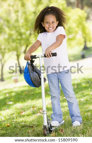 Young girl outdoors on scooter smiling