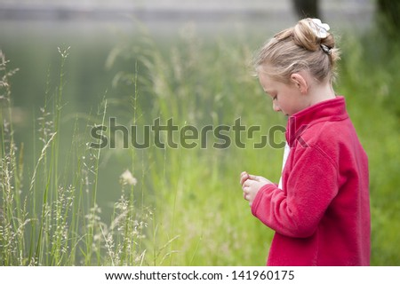 young girl outdoors playing with grass sprites - stock photo