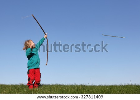 Young girl outdoors with bow and arrow - stock photo