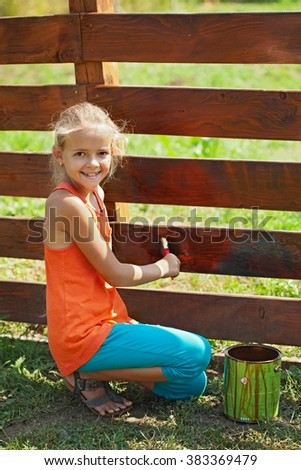 Young girl painting a wooden fence on a summer day - stock photo