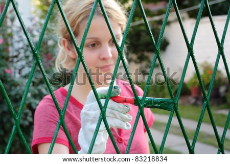 Young girl painting fence to green color, selective  focus on brush