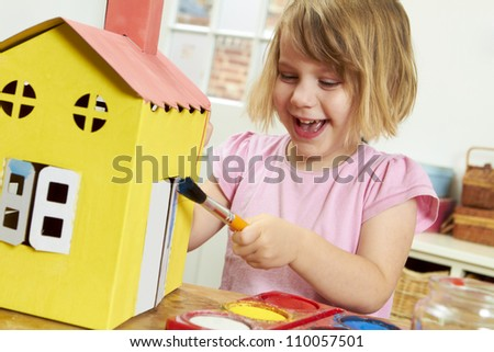Young Girl Painting Model House Indoors - stock photo