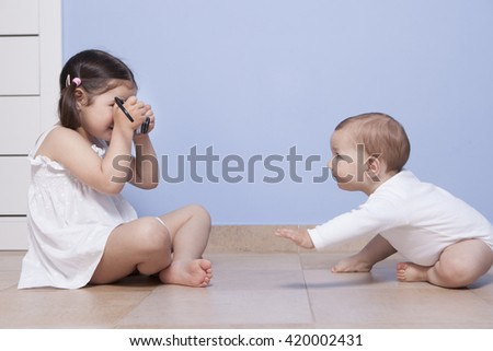 Young girl photographer. Pretty little sister taking pictures to her baby brother with old analog camera - stock photo