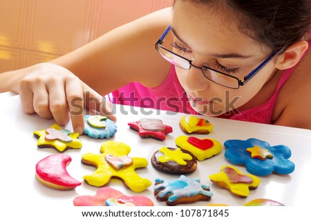 Young girl picking up one of many colorful and delicious cookies on a white table - stock photo