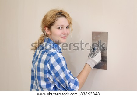 Young girl  plastering wall with trowel  in her home