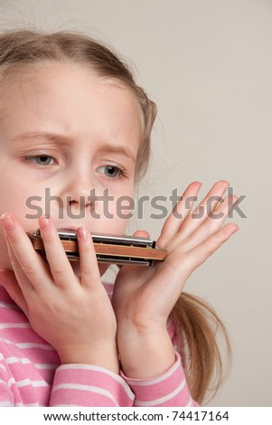 Young girl play blues harmonica