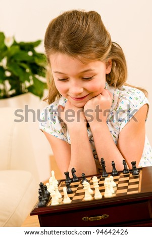 Young girl play chess cute smile alone at home