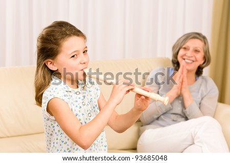 Young girl play flute with proud grandmother happy teacher clapping - stock photo