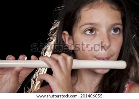 Young girl playing a fife on a dark background