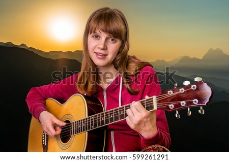 Young girl playing acoustic guitar in mountains at the sunset
