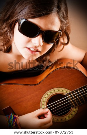 Young girl playing acoustic guitar wearing sunglasses. Portrait orientation.