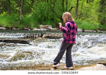 Young Girl - playing by a stream in the woods, tentatively dipping her toe in the water.