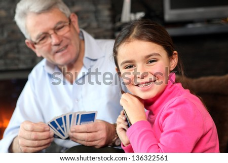 Young girl playing cards with grandpa - stock photo