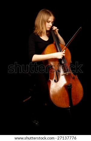 young girl playing cello on black background - stock photo