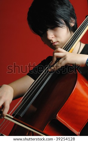 young girl playing cello on red background - stock photo