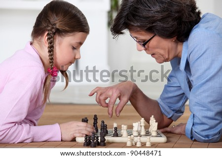 Young girl playing chess with grandma - stock photo