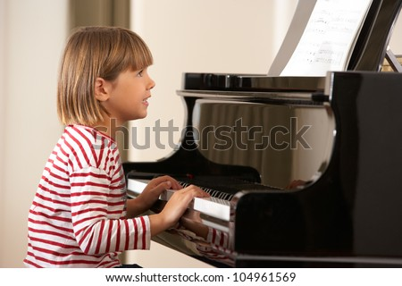 Young girl playing grand piano at home - stock photo