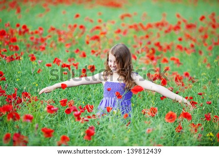 Young girl playing in a poppy field standing amongst the colourful red flowers with her arms outspread - stock photo