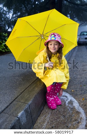 Young girl playing in rain - stock photo