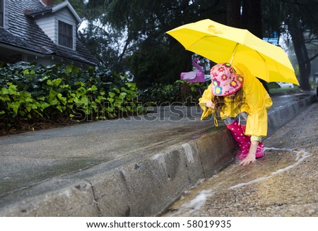 Young girl playing in rain 5 - stock photo