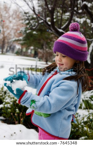 Young Girl Playing in Snow.  Hands in motion. - stock photo