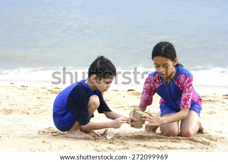 Young girl playing in the sand at the beach with younger brother - stock photo