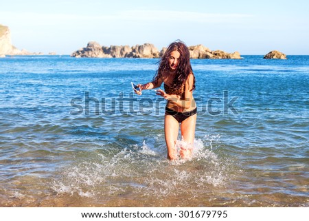 young girl playing in the water of the sea at a beach in Somerset, England - stock photo