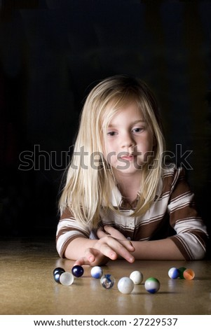 Young girl playing marbles on concrete floor. - stock photo