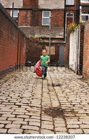 Young girl playing on cobble stoned alley - stock photo