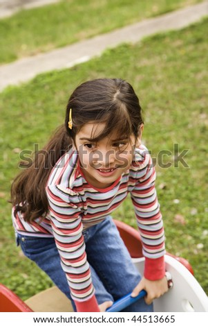 Young girl playing outside on playground. Vertically framed shot. - stock photo