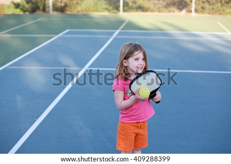Young girl playing Pickleball on an outdoor court.  - stock photo