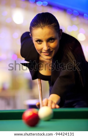 Young girl playing snooker - stock photo