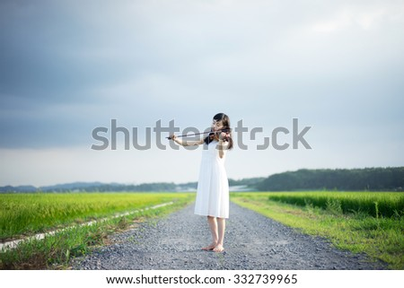 young girl playing violin on a country road - stock photo