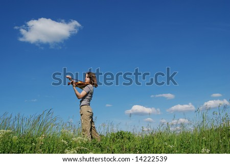 Young girl playing violin over blue sky and clouds on meadow