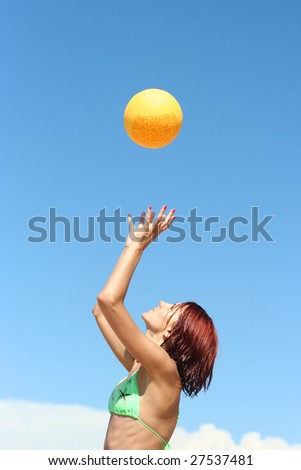 young girl playing volley-ball on the beach