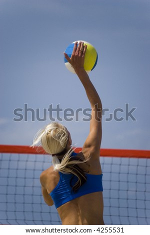 Young girl playing volleyball in the beach - stock photo