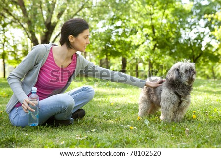 young girl playing with a dog in the park - stock photo