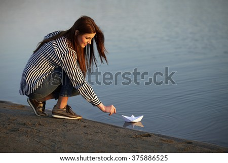 Young girl playing with a paper boat on the shore of a lake - stock photo